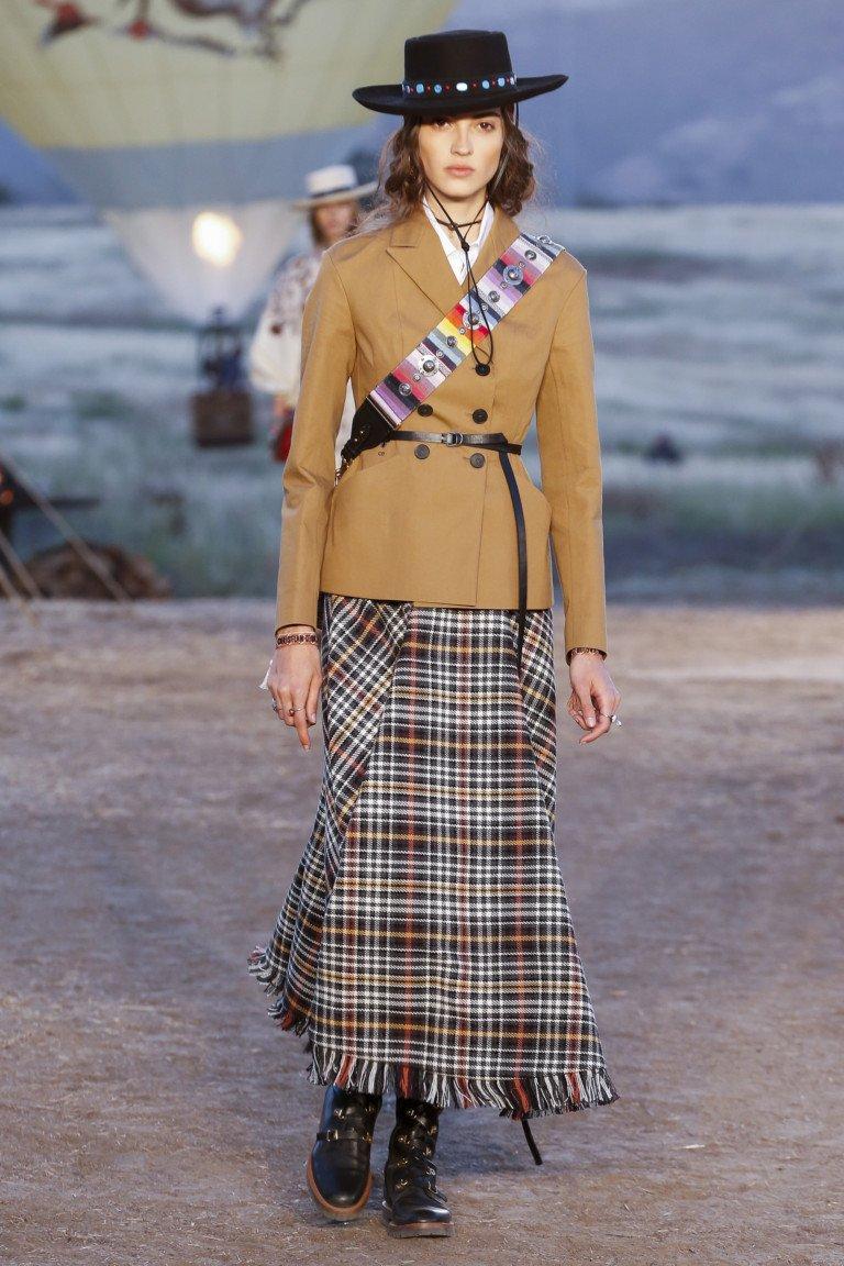 Светло-коричневый пиджак с черным ремешеом и длинной клетчатой юбкой.