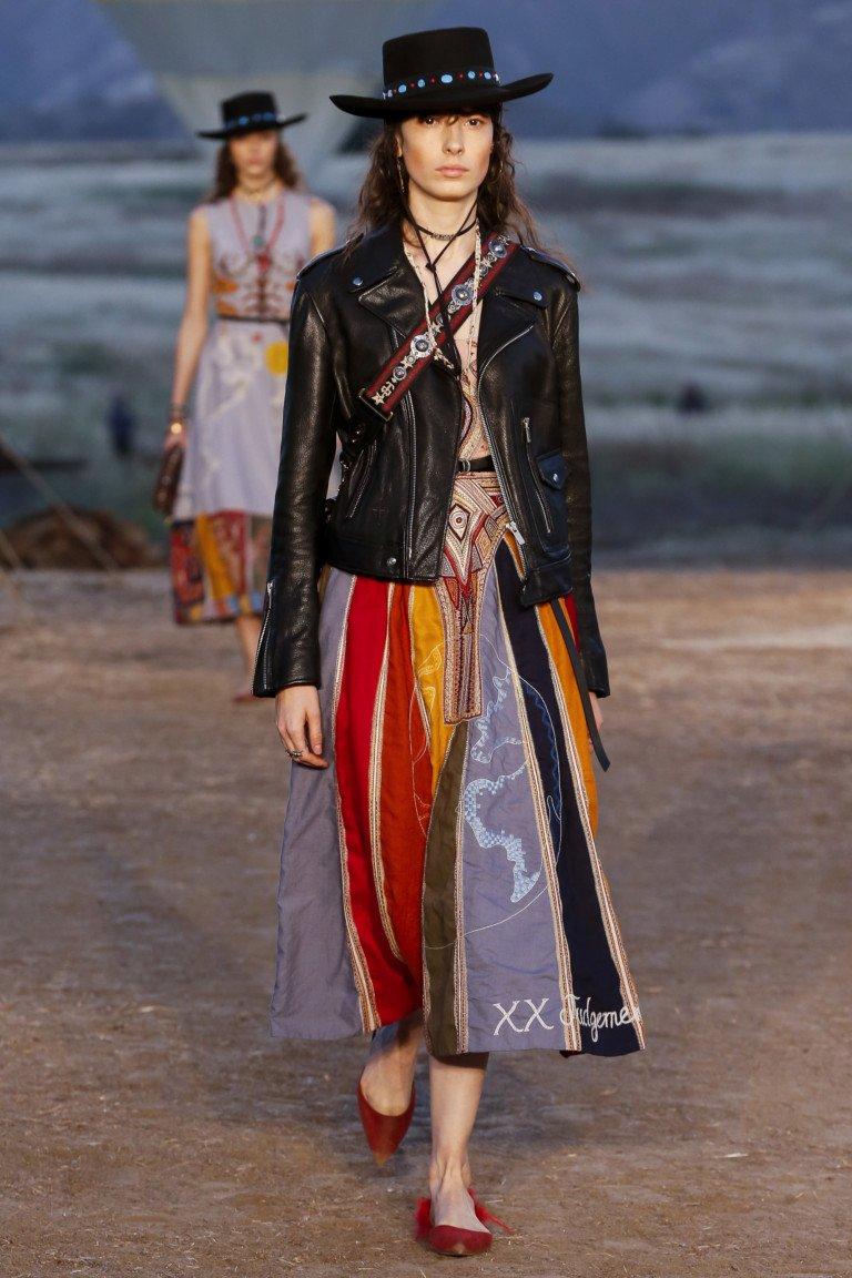 Черрная кожаная куртка с яркой юбкой с принтом в разноцветную полоску.
