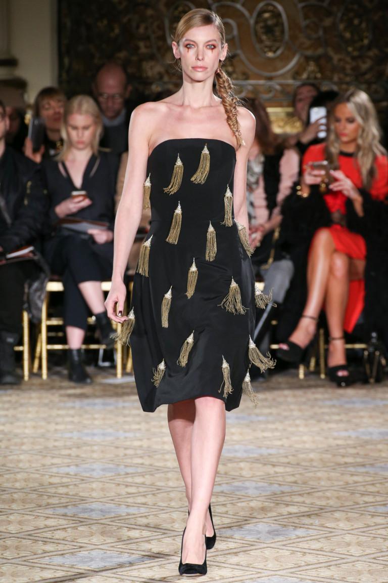 Черное платье декольте с золотистыми кистями.