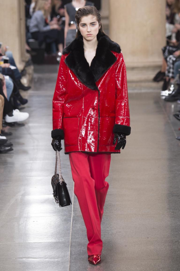Красная лакированная кожаная куртка с большим отложным меховым воротником и манжетами с красными прямыми брюками и туфлями.