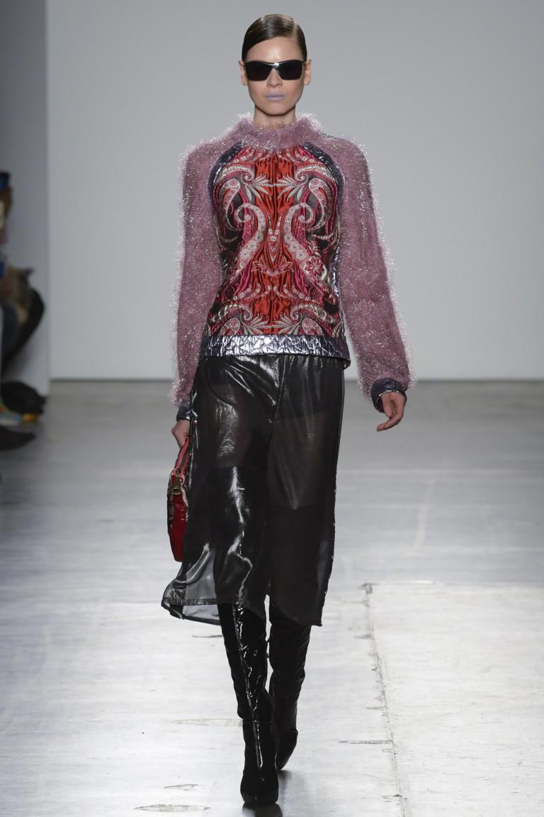 Вязаная с большим ворсом кофта с большим рисунком с черной юбкой и черными лакированными сапогами.