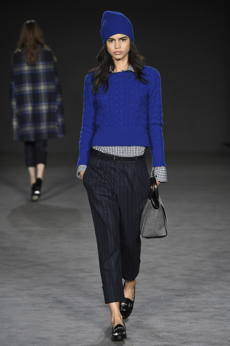 Синяя вязаная кта и шапочка с черными в полоску брюками с манжетами.