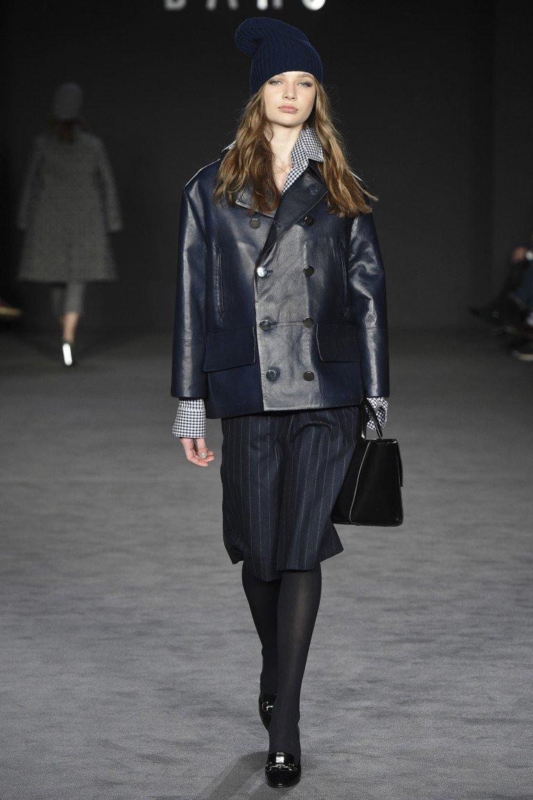 Элегантная черная кожаная куртка с черной юбкой в полоску.