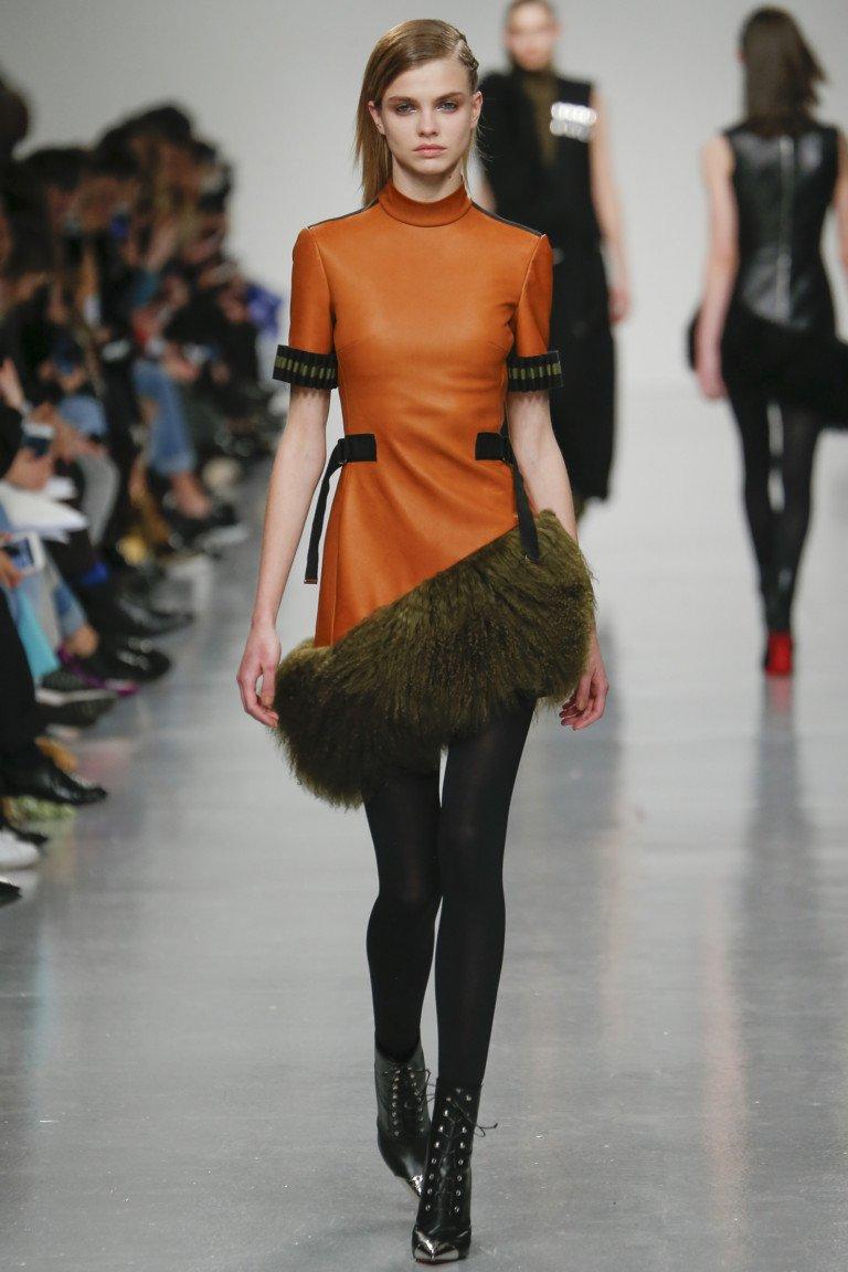 Короткое кожаное платье оранжевого цвета с большим мехом.