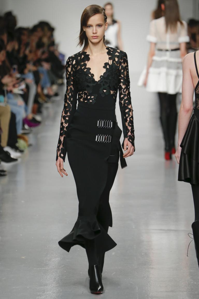 Черное узкое платье годе с кружевными длинными рукавами и глубоким кружевным вырезом.