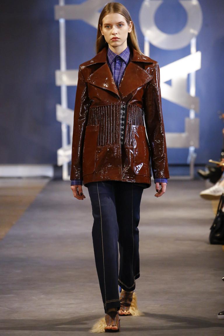 Лакированная кожаная куртка коричневого цвета с большими накладными карманами отлжным воротником и черными брюками.