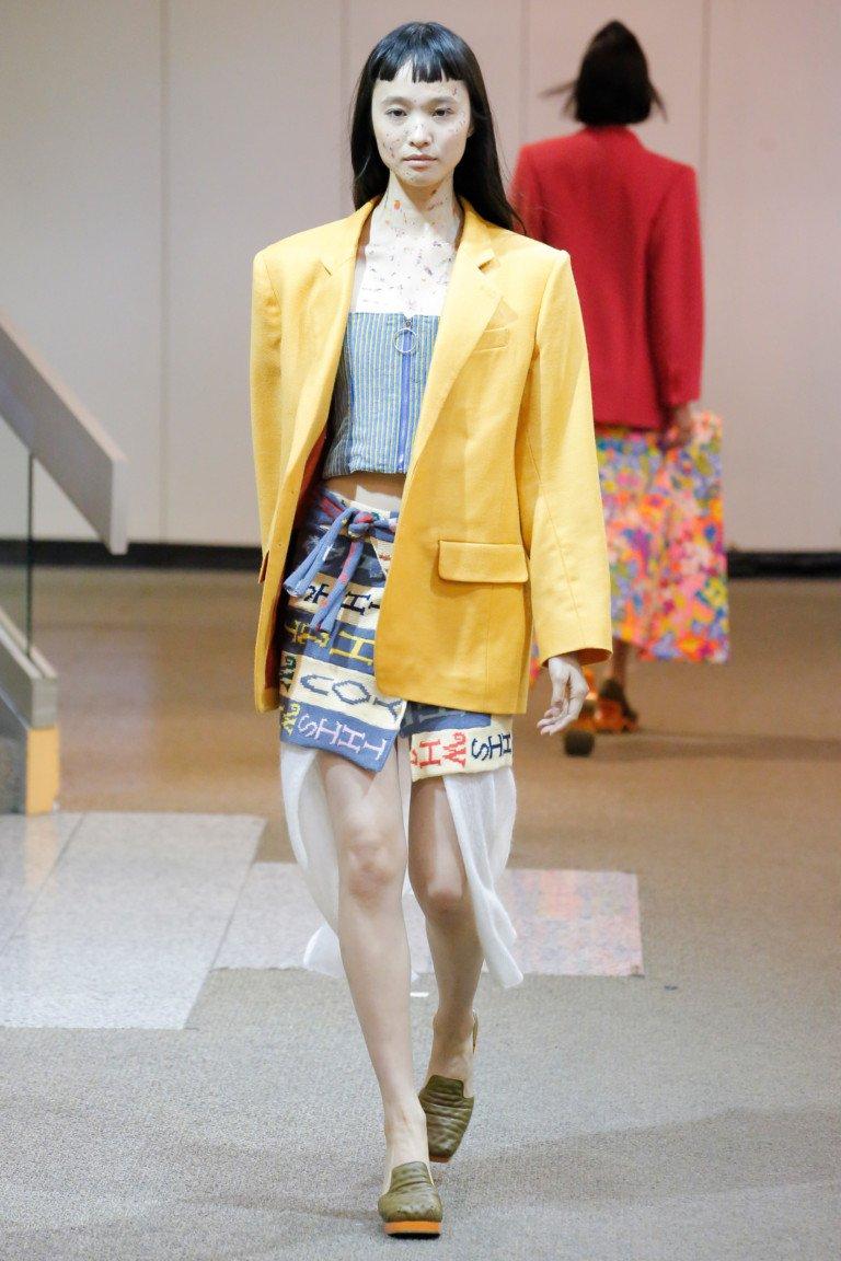 Желтый пиджак с короткой юбкой с принтом.