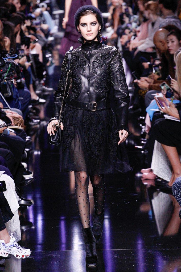 Черная кожаная куртка с рисунком с черной прозрачной юбкой и черными чулками в горошек.