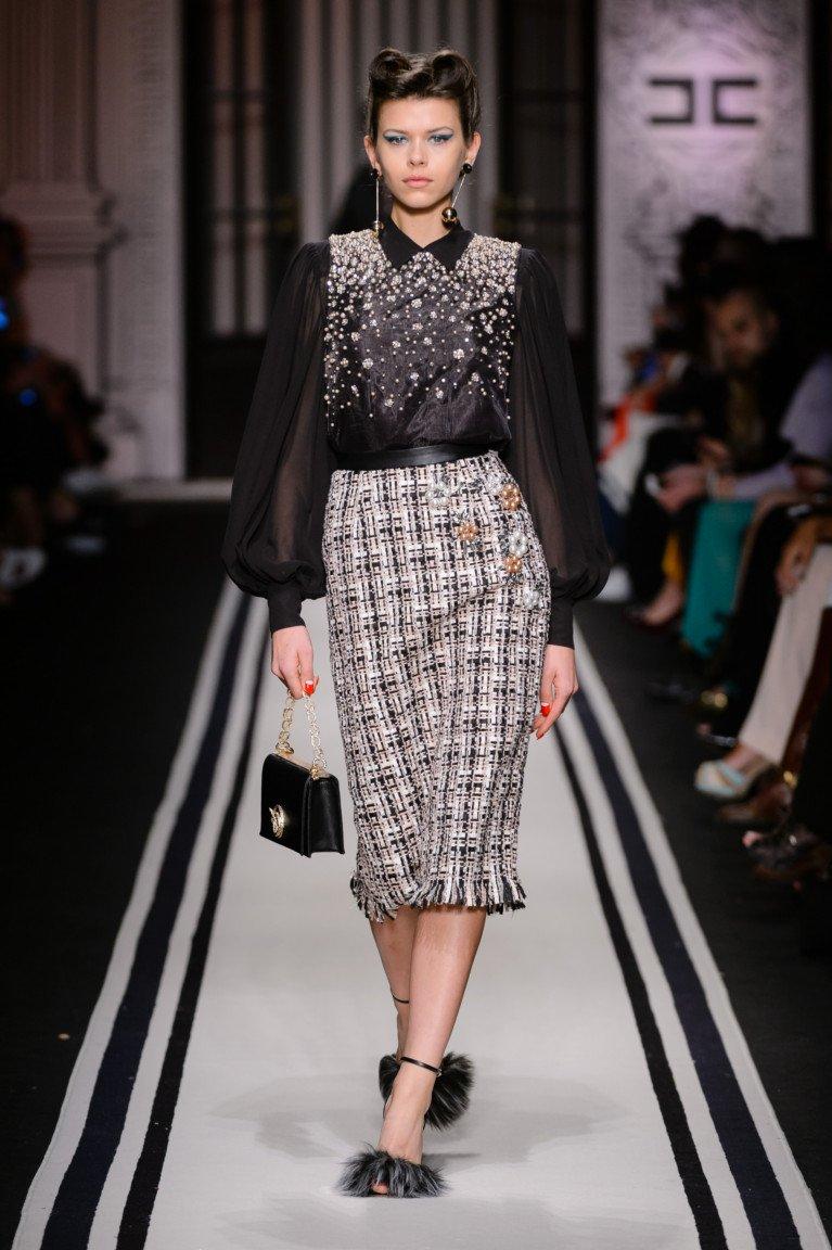 Черная блузка с белым горошком с длиннми прозрачными рукаами и юбка в клетку с бахромой.