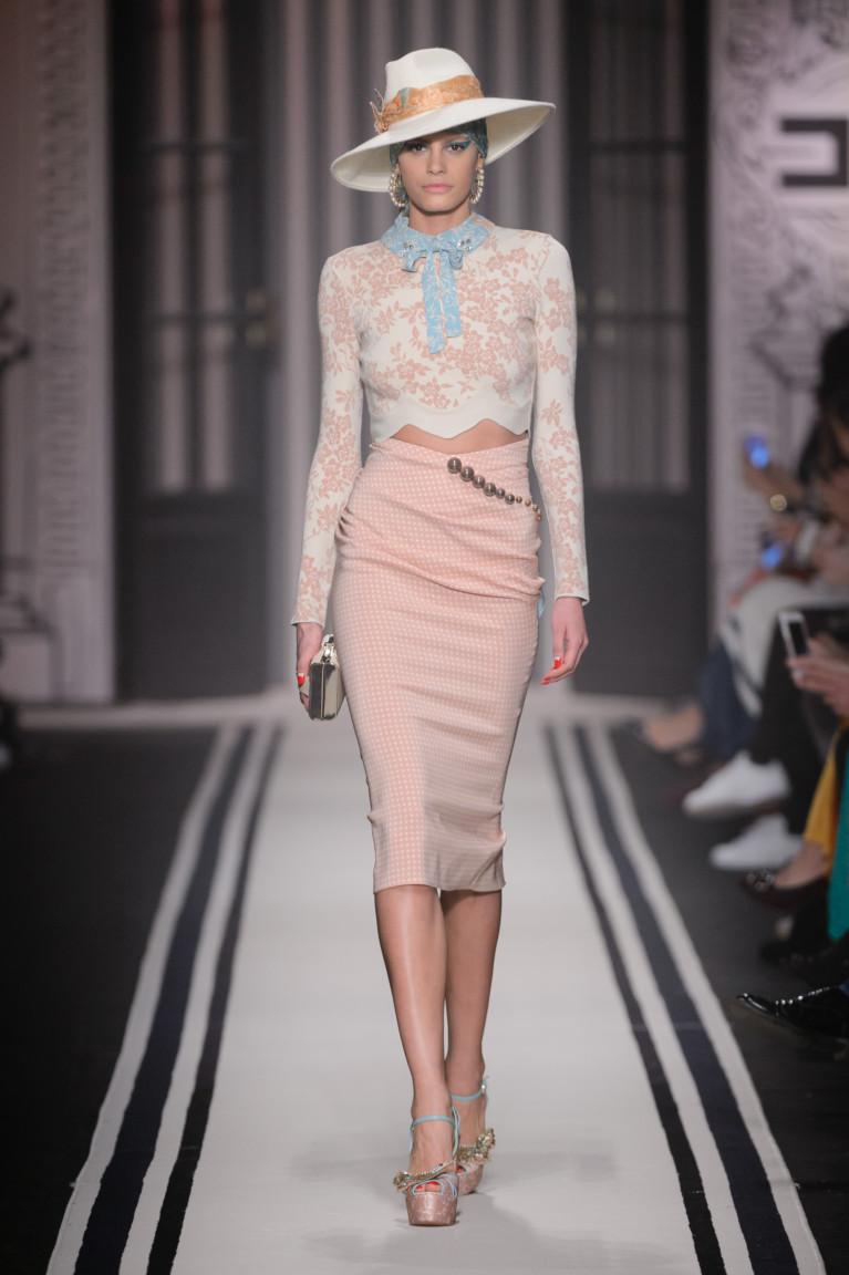 Элегантная кофта розового цвета с принтом и обтягивающая юбка в мелкую клетку.
