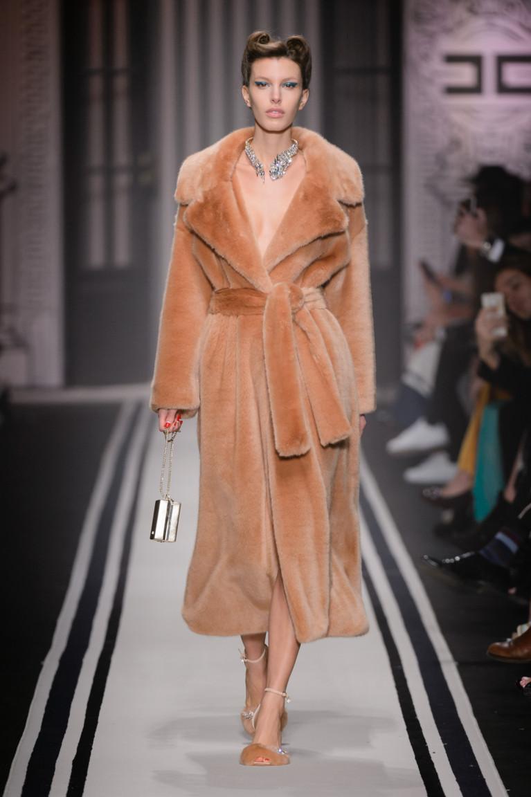 Светло-коричневая шуба с большим отложным воротником и широким меховым поясом.