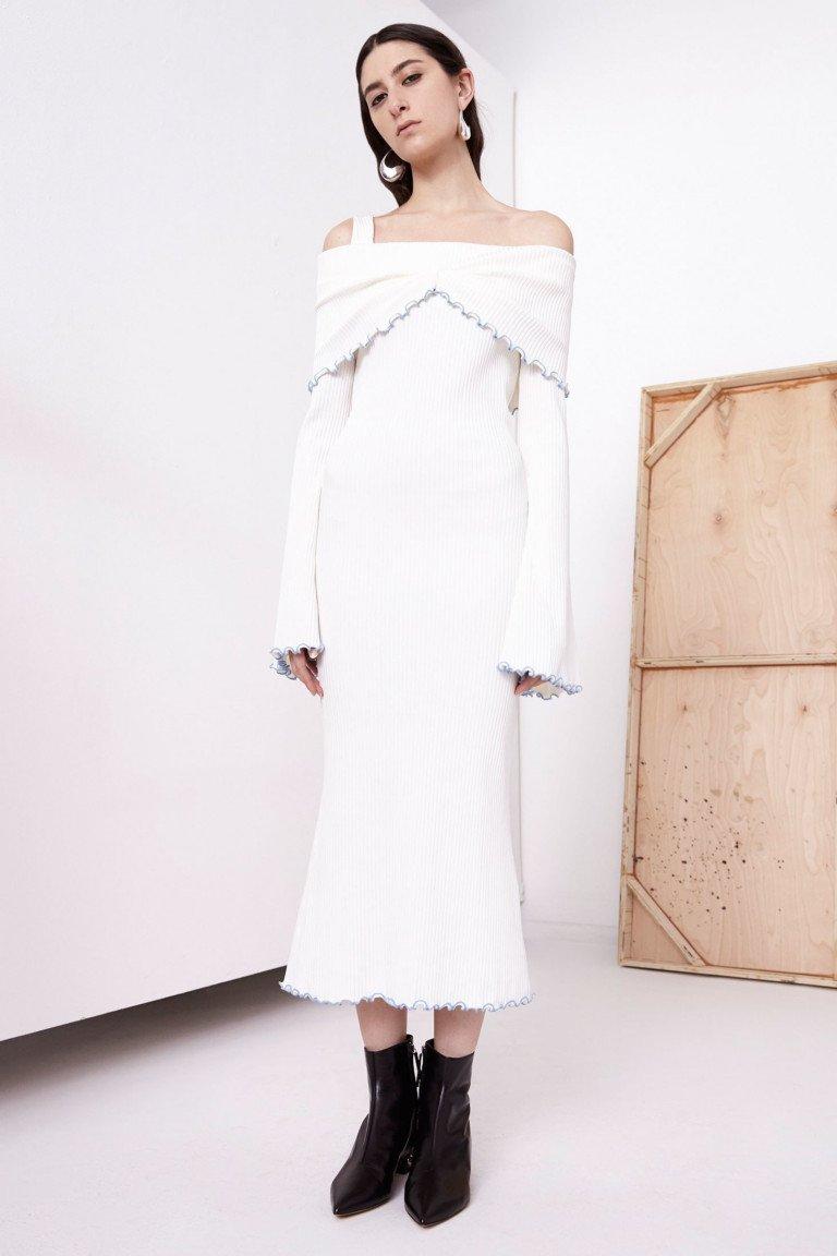 Платье белого цвета с длинными рукавами и  черными полусапожками.