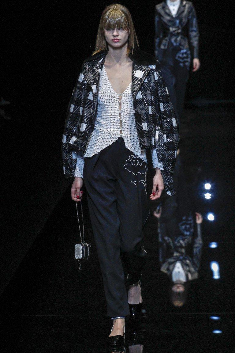 Белая блузка на пуговицах с черными брюками и ветровкой в клетку.
