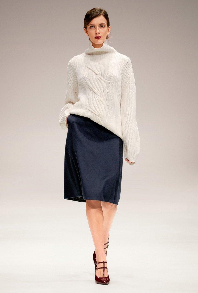 Белый свитер с ажурной вязкой с длинными рукавами и черной юбкой.