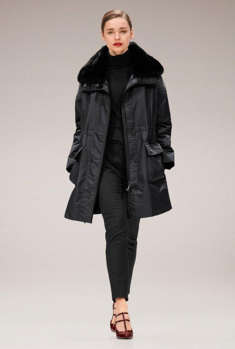 Черная куртка с большим меховым воротником и черными узкими джинсами.