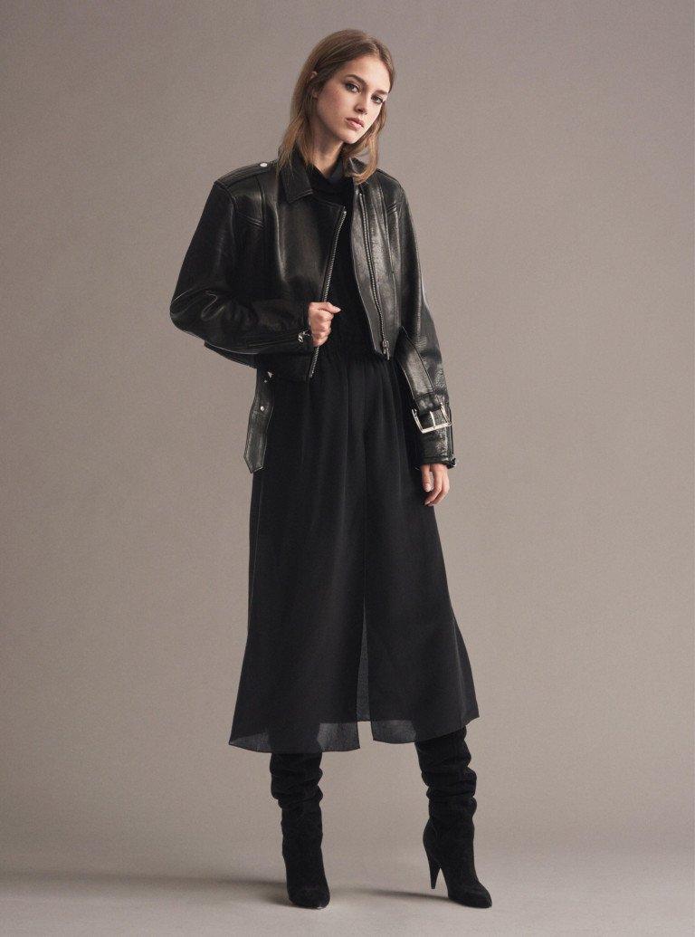 Короткая черная кожаная куртка с широким ремнем и полупозрачной черной юбкой и черными замшевыми сапогами.
