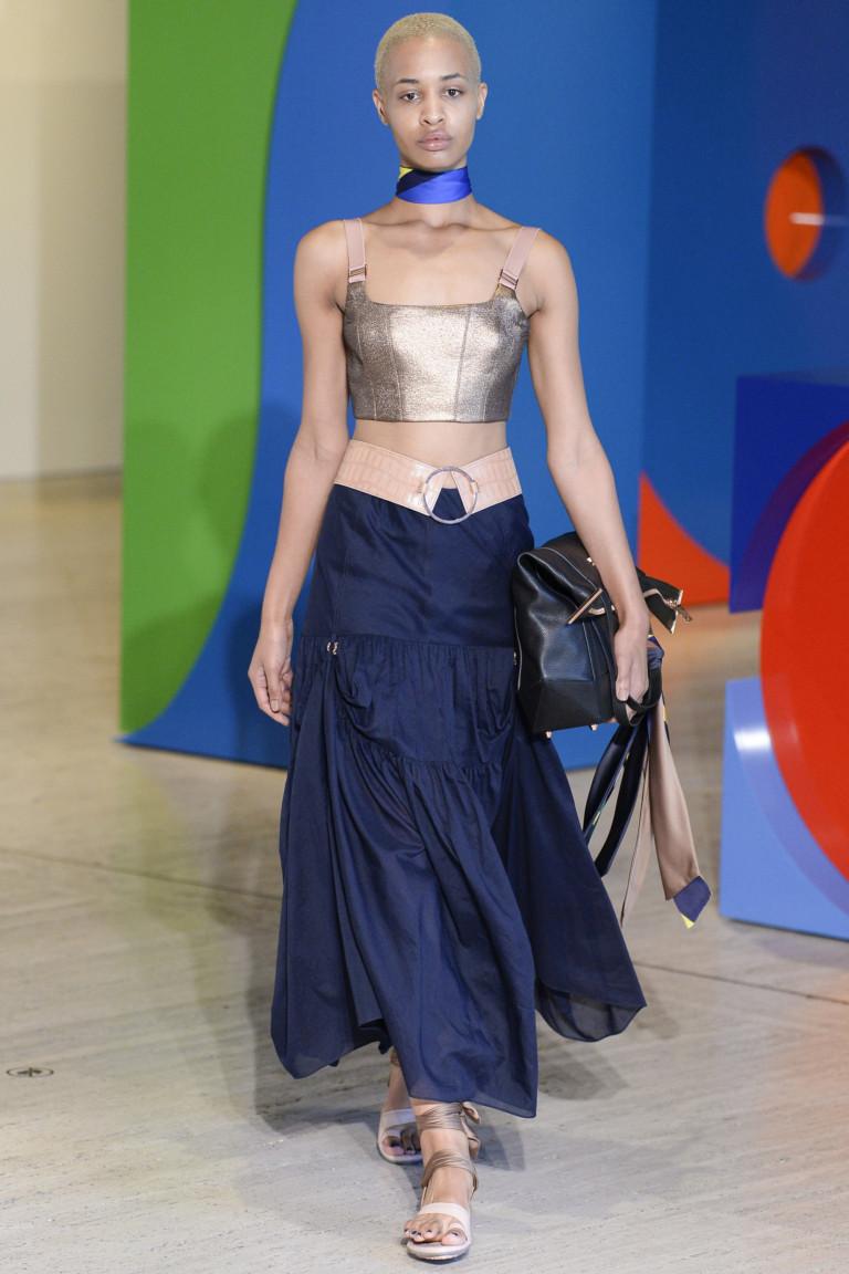 Расклешенная длинная синего цвета юбка с широким поясом с коротким топом золотистого цвета.