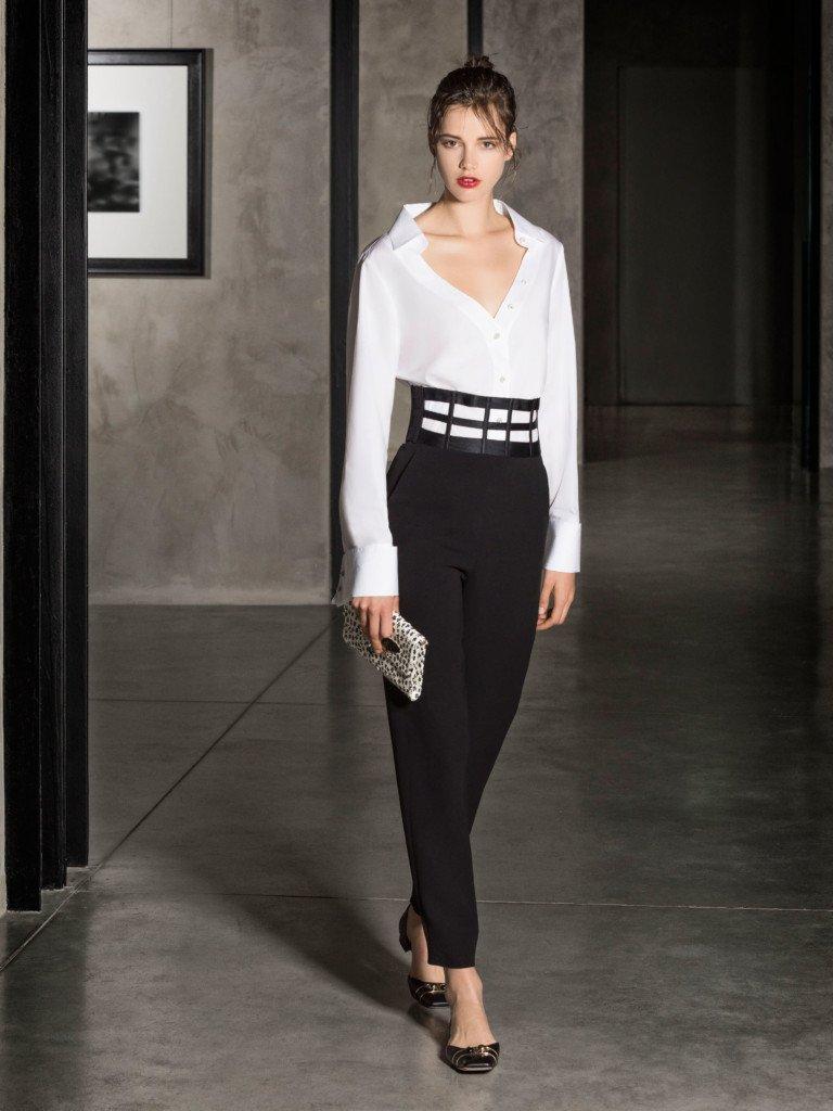 Белая блуза с глубоким вырезом и длинными рукавами и черными зауженными брюками с широким поясом