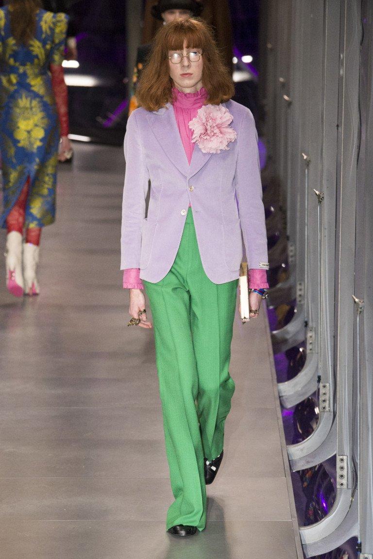 Светло-фиолетовый пиджак с большим розовым бантом и зелеными расклешенными брюками.