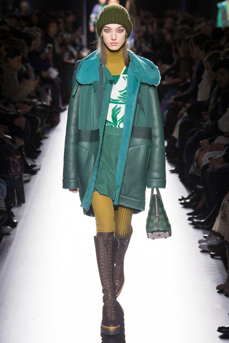 Зеленого оттенка кожаная с мехоми капюшеном куртка с всокими сапогами на толстой подошве с о шнуровкой.