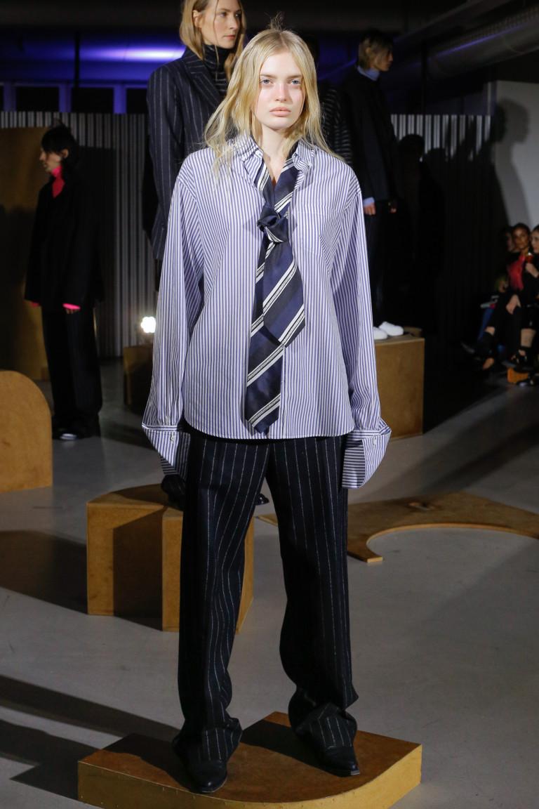 Рубашка в полоску с длинными рукавами и длинными черными брюками в полоску.