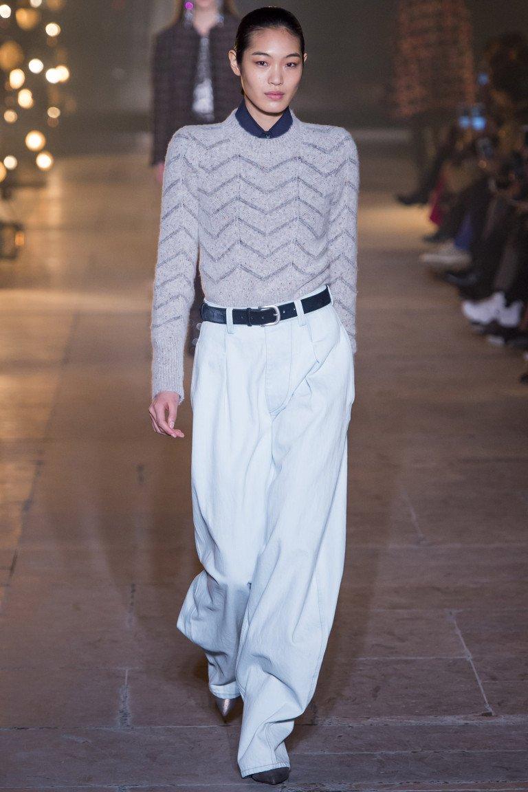 Светло серая кофта с полосатым принтом и широкими белыми брюками.