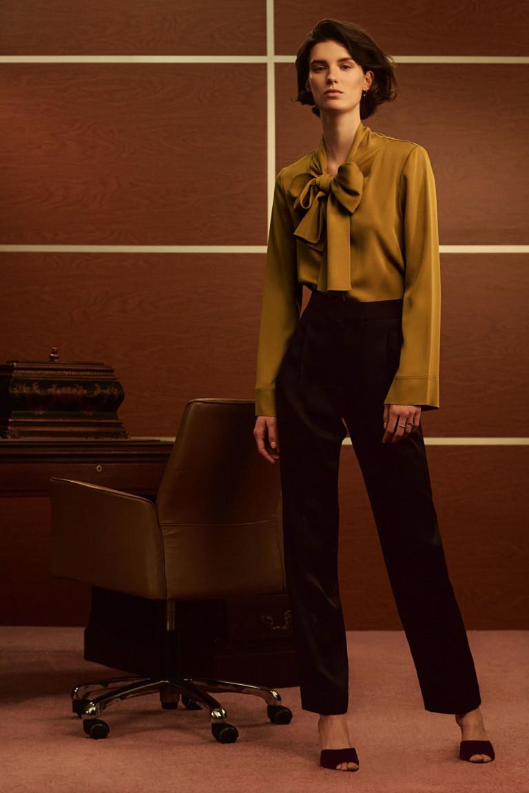 Блузка песочного цвета с длинными рукавами и большим бантом с черными брюками.