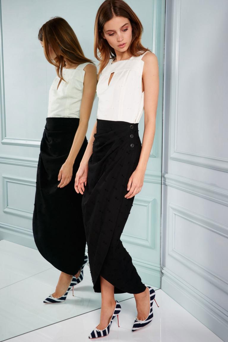 Белая блузка с узкой черной юбкой и узкими туфлями в полоску на высоком тонком каблуке.