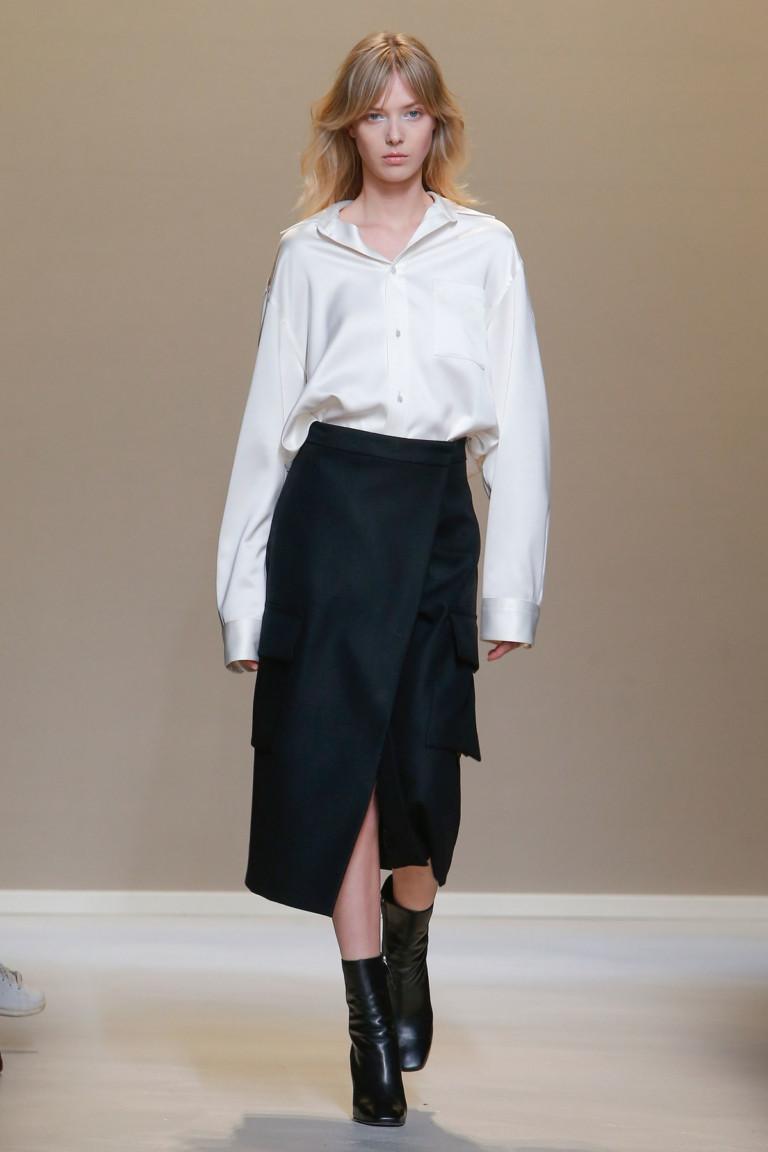 Белая блузка с длинными рукавамии черная юбка с запахом.