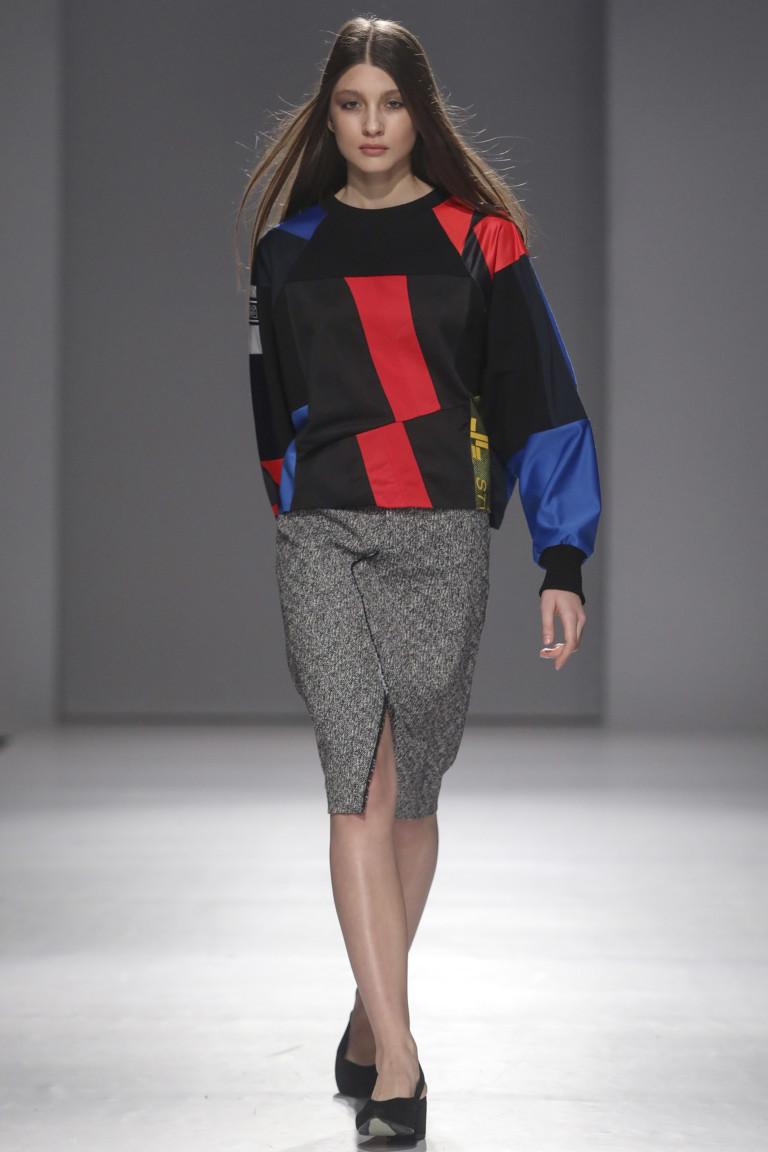 Черная кофта с большими разноцветными вставками и серая узкая юбка с разорезом.
