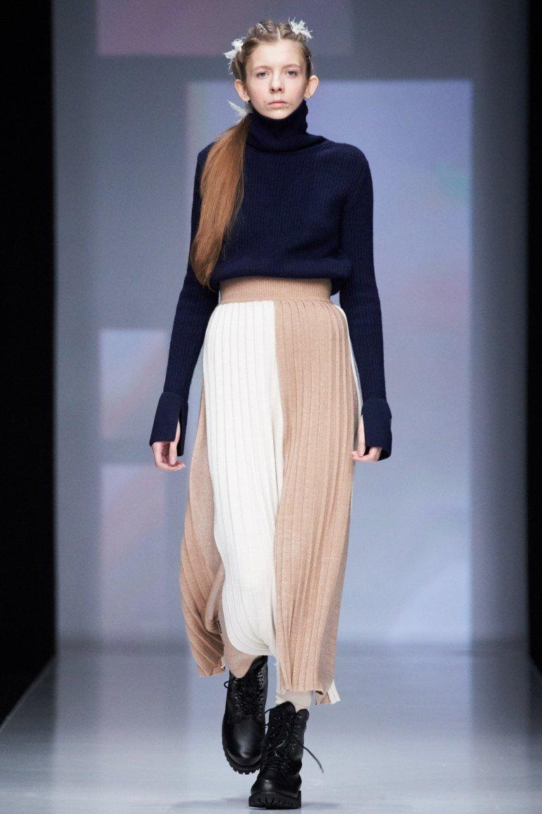 Черный свитер с длинными рукавами и длинная вязаная юбка белого и бежвого цвета.