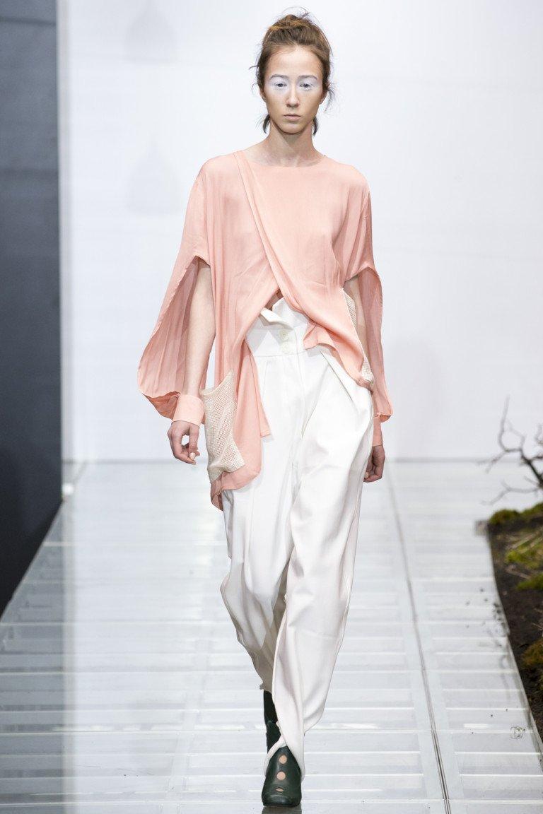 Розовая ассиметричная блузка с широкими белыми брюками.
