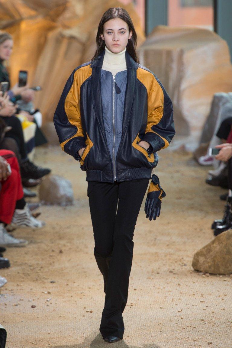 Черная куртка с большими полосами оранжевыми на рукавах с черными брюками