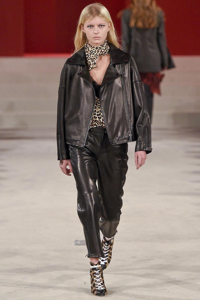 Темно коричневого цвета кожаные куртка и брюки с блузкой, шарфом и ботильонами со шнуровкой леопардовой расцветки.