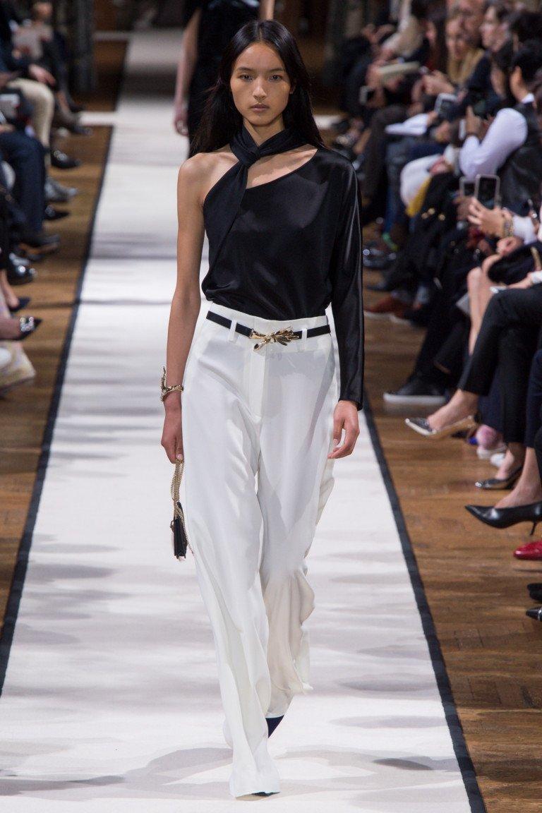 Черная атласная блузка с одним рукавом и длинные широкие белые брюки.
