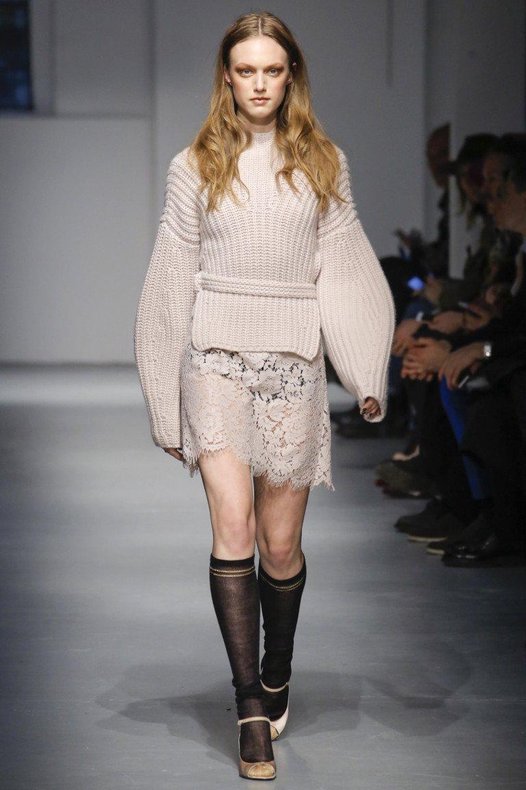 Бежвого цвета шерстяная кофта круной вязки и кружевная короткая юбка.