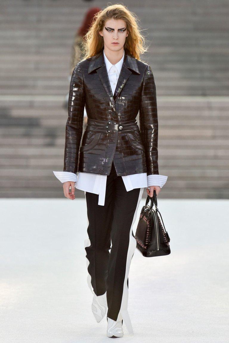 Темно коричневого цвета кожаная куртка с белой длинной рубахойи черными брюками с лампасами белого цвета.