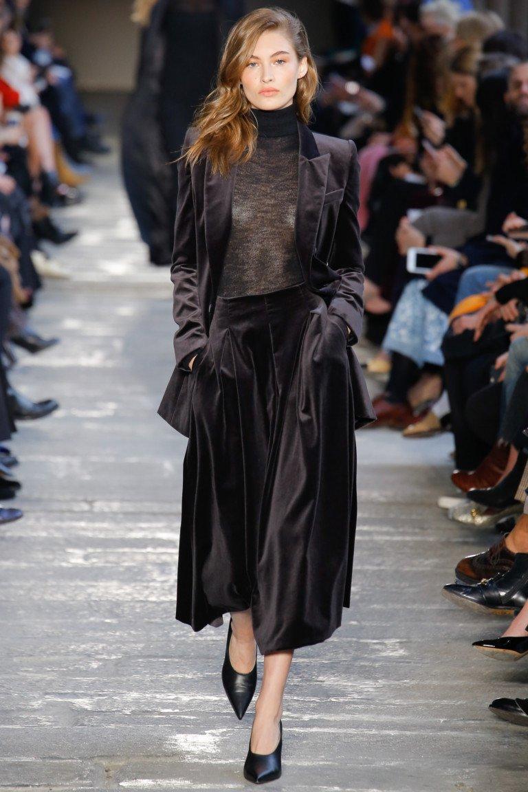 Темно-коричнего цвета пиджак и расклешенная юбка и черные туфли лодочка