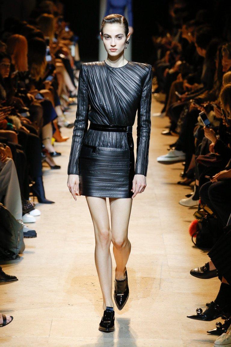 Короткое черное кожаное платье в ассиметричную полоску с черными туфлями.