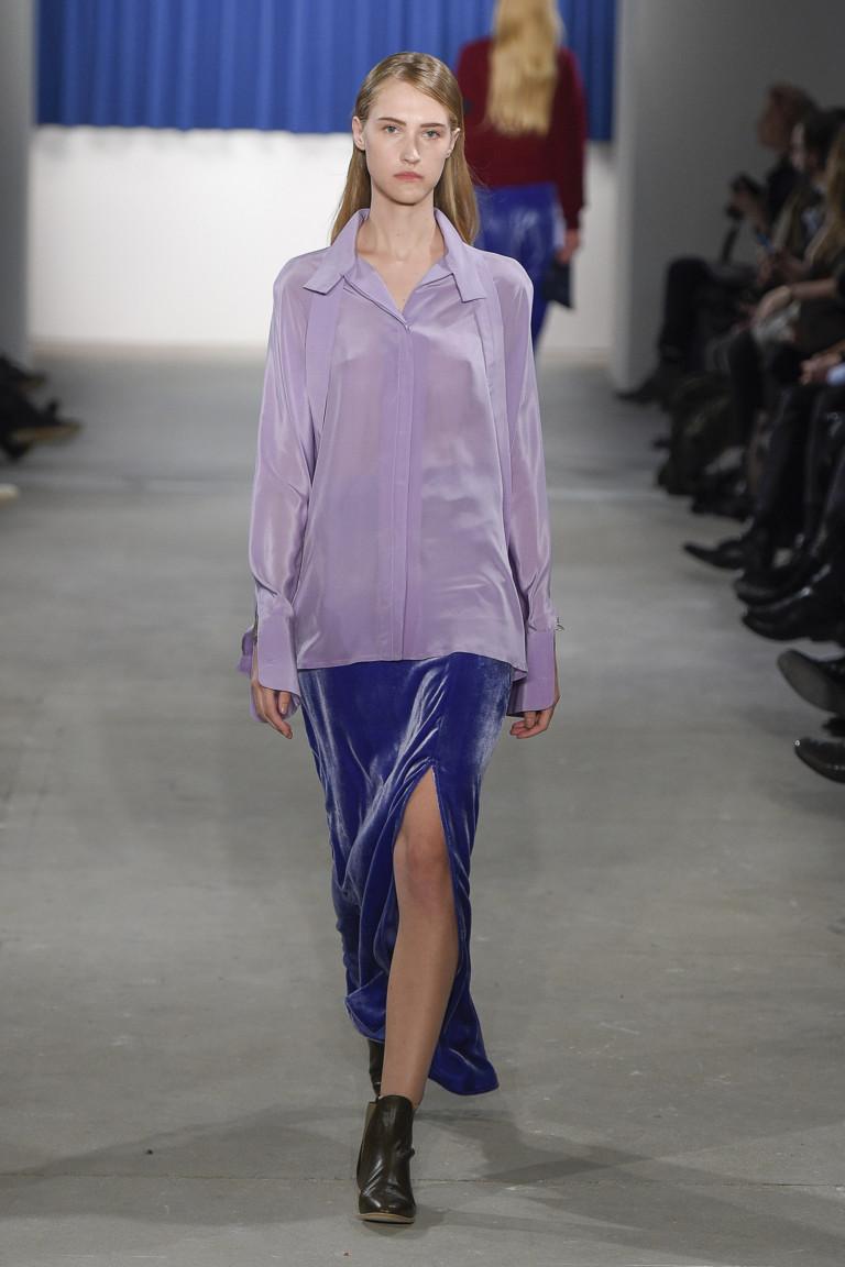 Нежно фиолетового цвета блузка с синей длинной юбкой с большим разрезом.