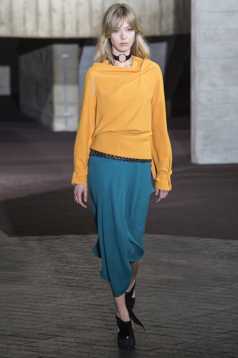 Желтая блузка с синей ассиметричной юбкой и черными туфлями.