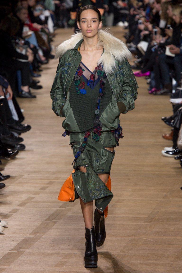 Куртка темно зеленого цвета с принтом и юбка с многочисленными молниями.