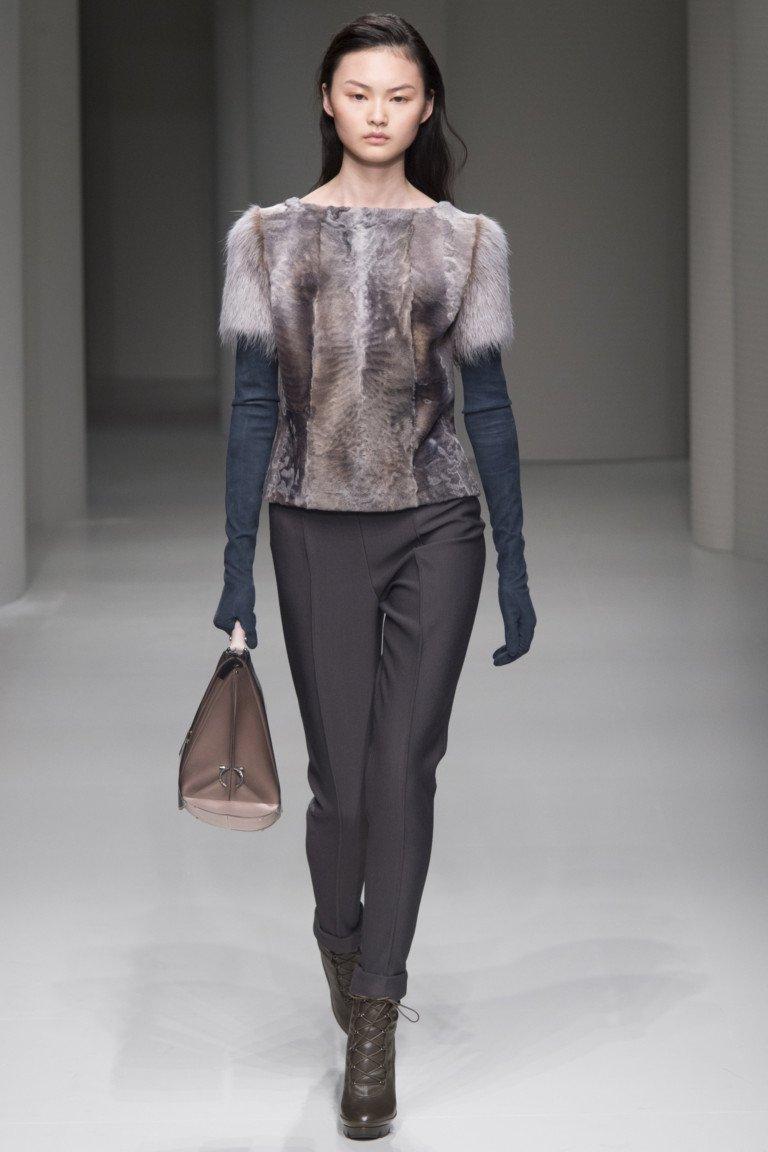 Меховая кофта с коротким рукавом с длинными черными перчатками и узкими черными брюками.