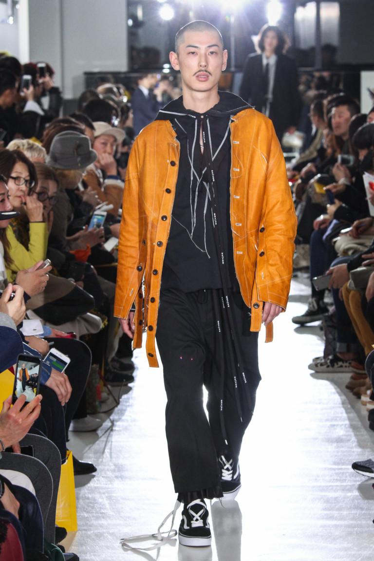 Ярко оранжевая мужская кожаная куртка со спортивным костюмом и кроссовками.
