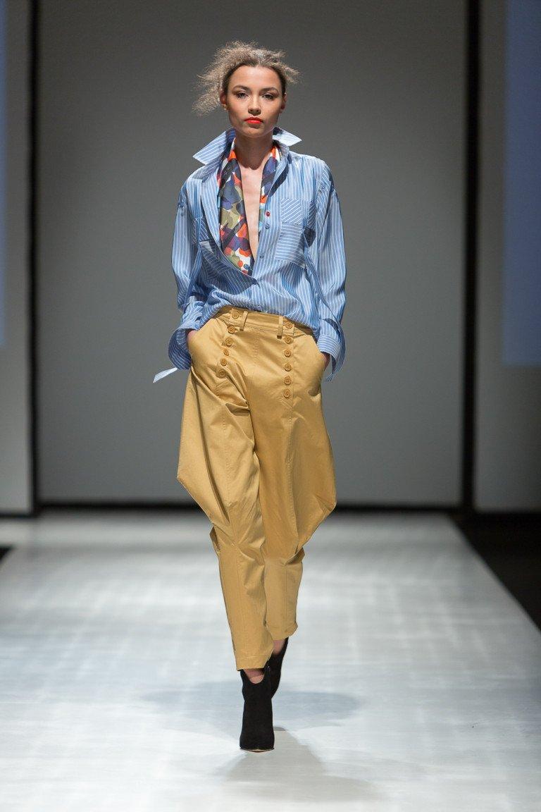 Голубая рубашка в полоску со светло-коричневыми брюками.