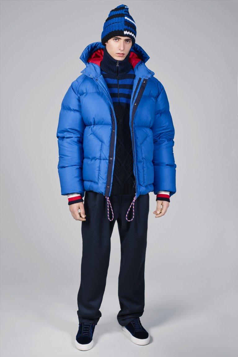 Ярко синяя мужская пуховая куртка с вязанной шапочкой и спортивными брюками.