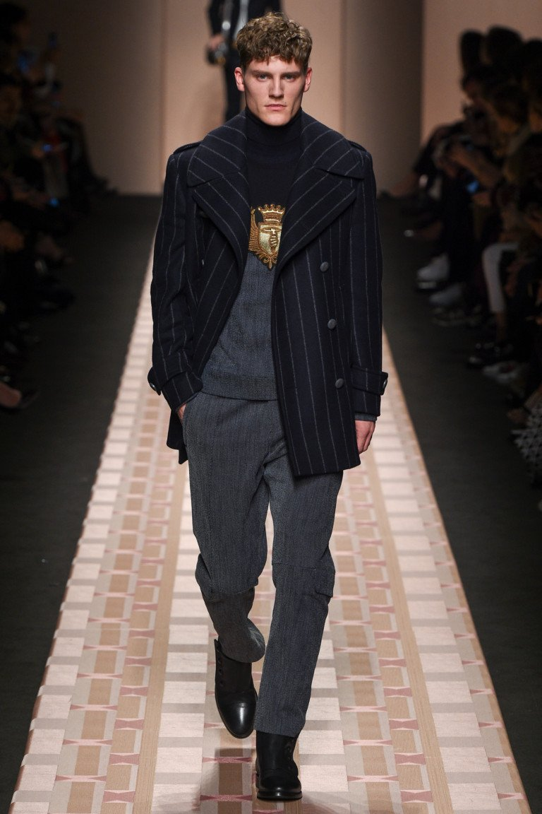 Черное в полоску укороченное мужское пальто с серыми классическими брюками.