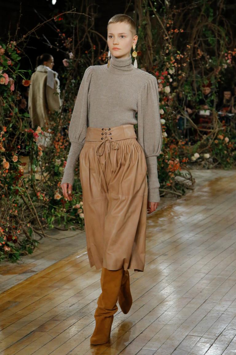 Серая кофта с длинными рукавами и большими манжетами и светло-коричнего цвета кожаная юбка на широком поясе со шнуровкой