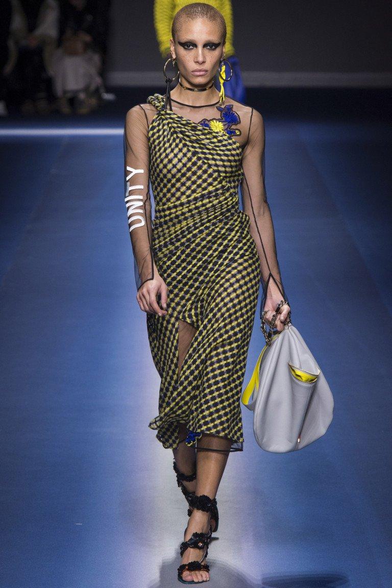 Платье-сарааф в черно-желтую клетку с черной прозрачной блузкой с длинными рукавами.