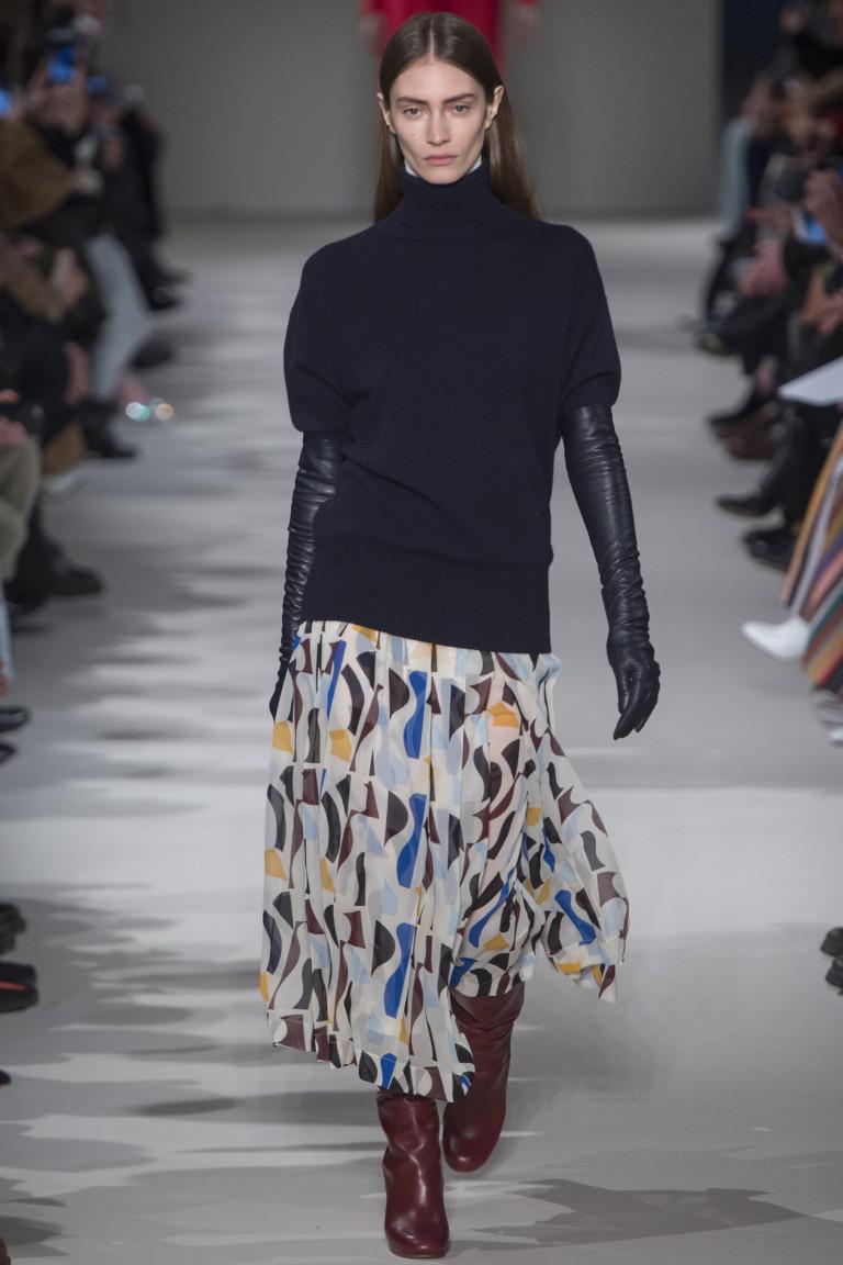 Черный свитер скороткими рукавами с длинными перчатками и юбкой из легкой ткани с разноцветным принтом.